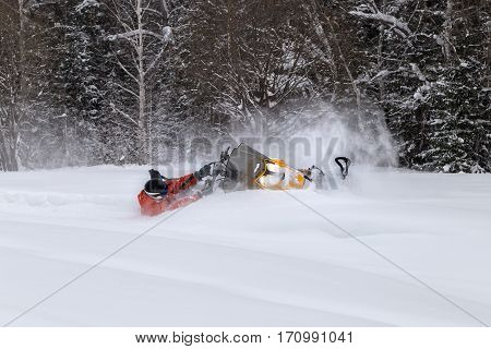 The sportsman on snowmobile fell into a deep snowdrift. Winter snowmobiling in the mountains of the Urals.