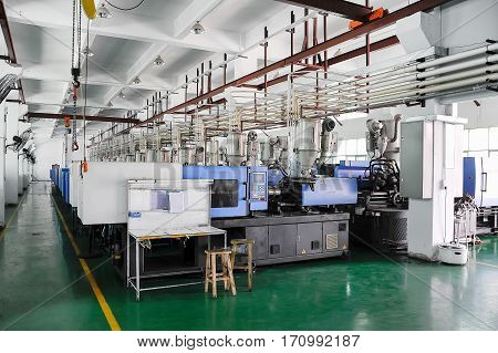 Row of plastic injection CNC machines at empty workshop