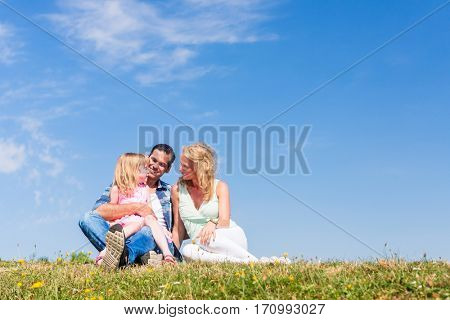 Girl on dads lap, Mom sitting next to them in field
