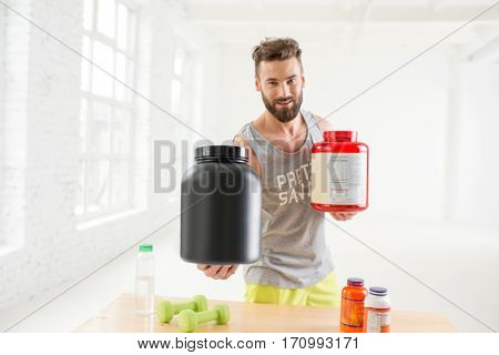 Athletic man holding bottles with sports nutriton in the white gym interior. Blank bottles to copy paste your label