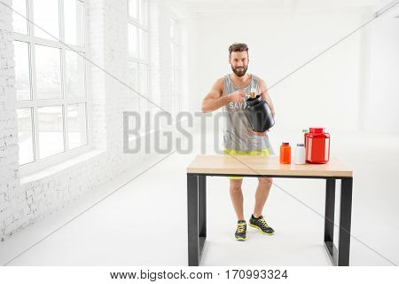 Athletic man in sportswear pouring with scooper protein powder in the white gym interior
