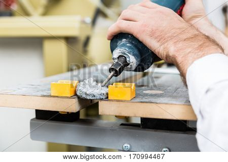 Stonemason shaping ornament with pneumatic chisel