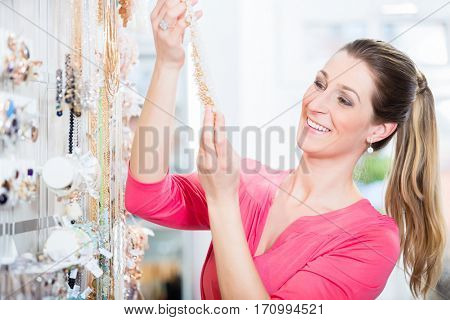 Woman shopping in store looking at trinket necklace