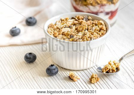 Homemade fitness granola with yoghurt and blueberries on white kitchen table background