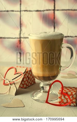 Coffee Latte with gift boxes, envelope and paper hearts. Pink, red, white colors on bright background. Love, Valentine's day concept. Vertical, toned