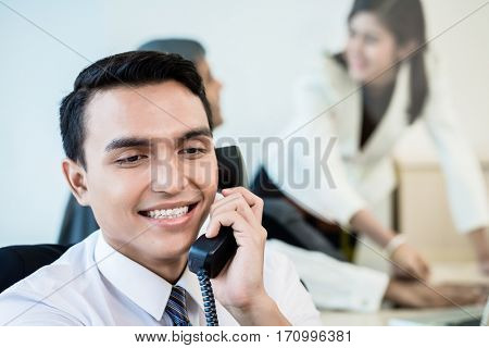 Asian employee in office making a business call