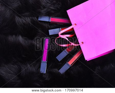 Lipsticks With Present Bag On Fur Background