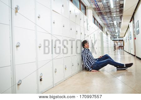 Portrait of smiling student sitting in locker room at college