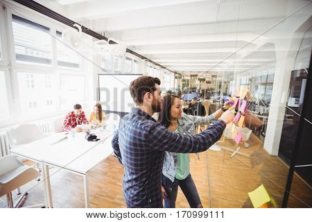 Photo editors looking at sticky notes on glass in meeting room at creative office