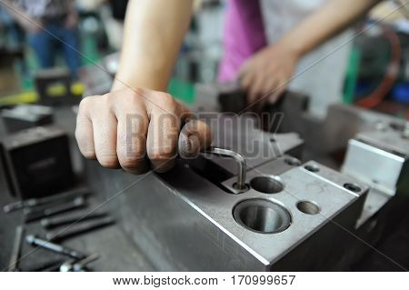 Worker's hand screwing while working with press form