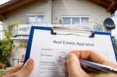 Close-up Of Person Hand Filling Real Estate Appraisal Document In Front Of House poster