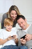 Family playing video game on smart-phone poster