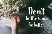 Life quote. Motivation quote on soft background. The hand touching purple flowers. Don't be the same be better. poster