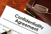 Confidentiality Agreement form on a table. Non-disclosure contract. poster