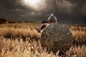 Confident incognito warrior going forward in attack with bronze rounded shield. Soldier in armor and helmet like spartan holding weapon front of himself. Dark clouds in sky. War in field. poster