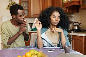 Young African male begging his girlfriend to forgive him. Husband asking his pretty wife for forgiveness after conflict sitting at table in kitchen. Angry woman refusing apologies from her man poster
