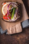 Danish sandwich with fish on the parchment closeup vertical poster
