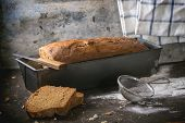Loaf of fresh homemade rye bread with wheat seeds and flour over dark table poster
