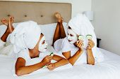 Mom and her 10 years old preteen daughter chilling in the bedroom and making clay facial mask. Mother with child doing beauty treatment together. Morning skin care routine. poster