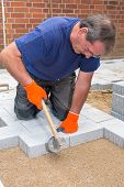Builder or contractor laying paving stones around a new house tamping them into position using a heavy mallet on a prepared sand base poster