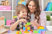 Woman and little boy playing lego game together poster