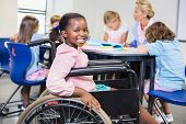 Disabled schoolgirl smiling in classroom at school poster
