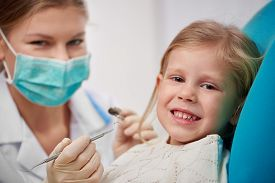 Happy smiling child sitting on dental chair ready to cure teeth. Portrait of woman dentist in mask with tools treating patient.