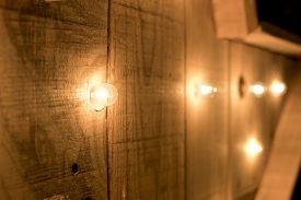 Small lights in a row on a wooden surface.