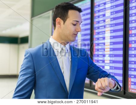 Businessman checking time in the airport, flight delay concept