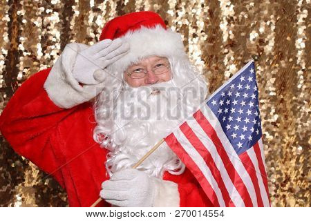 Santa Claus. Santa Claus holds an American Flag. Santa is all American. Gold Sequin background. Christmas Images.