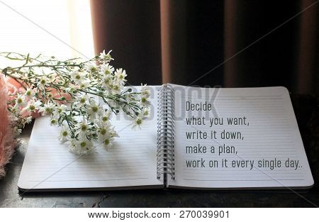 Inspirational Motivational Quote-decide what you want, write it down, make a plan, work on it every single day. An illustration of a note book written with white tinny flowers, brown curtain, soft pink fabric and natural light background. poster