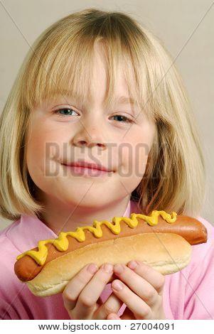 Little girl eating hot dog,Kid eating hot dog.