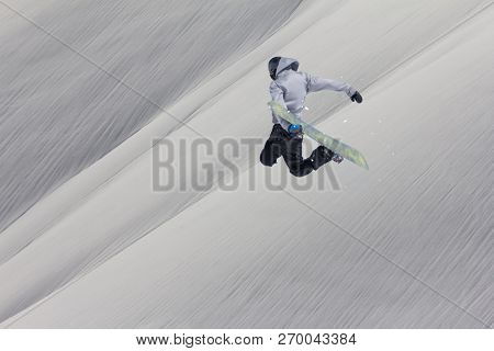 Snowboarder flying on the background of snowy slope. Extreme winter sports, snowboarding.