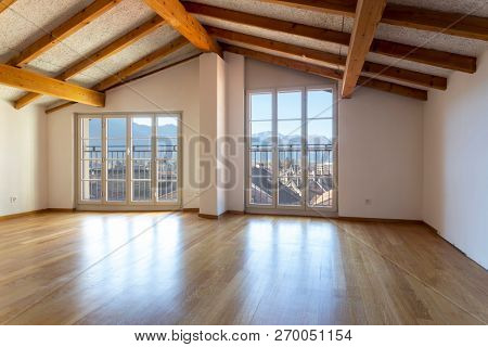 Room with wooden beams and large windows overlooking the Swiss Alps. Nobody inside