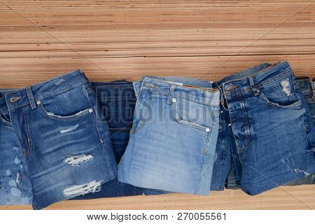 Stacked of different Blue t jeans on a brown wooden background