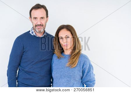 Beautiful middle age couple in love over isolated background Relaxed with serious expression on face. Simple and natural looking at the camera.