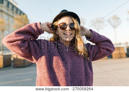 Outdoor Portrait Of A Smiling Teen Girl 13, 14 Years Old In A Hat And Sunglasses. City Background, G
