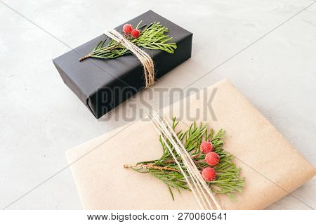 Wrapping Christmas gifts in recycled paper in rustic style. Xmas Gift boxes with craft paper, twine, coniferous branches, red berries and scissors on grey concrete background. Christmas gift pack poster