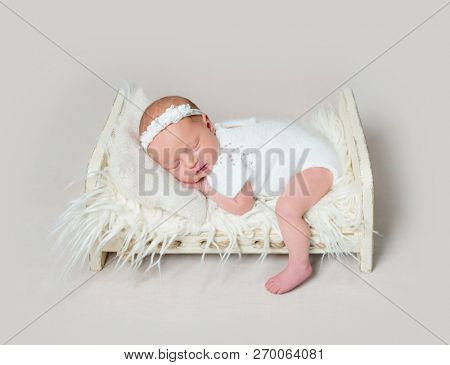 Lovely newborn baby girl sleeping on small crib lowered her small leg on the floor. Little child girl in white outfit with flowery headband
