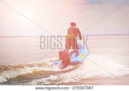 Silhouette Of Man Jumps On The Jetski Above The Water On The Wave
