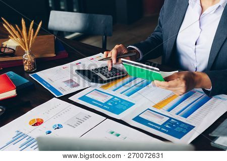 Businesswoman or banker hands holding saving account passbook and using calculator.Finances Saving Economy concept. poster
