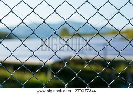 Wire Mesh Fence With Solar Panels Blurred Image Background.