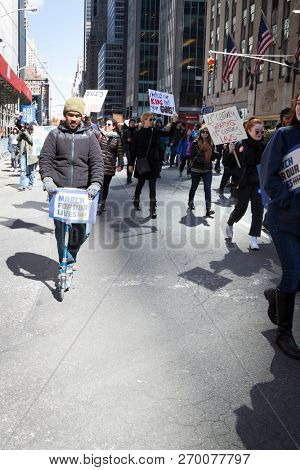 March For Our Lives: A young man rides on a scooter alongside other protesters at the march on 6th Ave to end gun violence, NEW YORK MAR 24 2018.