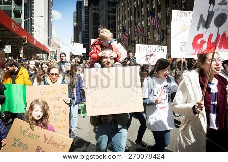 March For Our Lives: A man with a small child on his shoulders holds a sign that says Arms Are For Hugging at the national march to end gun violence, 6th Ave NEW YORK MAR 24 2018.