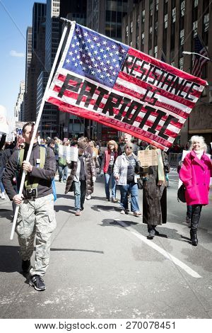 March For Our Lives: A protester carries a large American Flag that says Resistance Is Patriotic at the march on 6th Ave to end gun violence, NEW YORK MAR 24 2018.