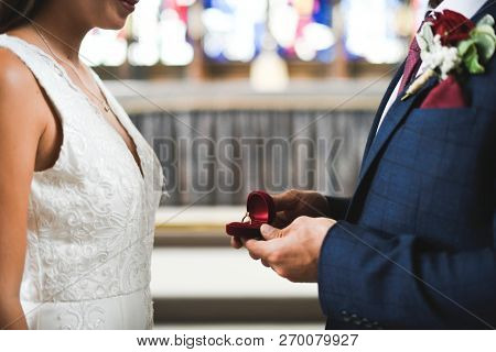 Groom taking out the wedding ring