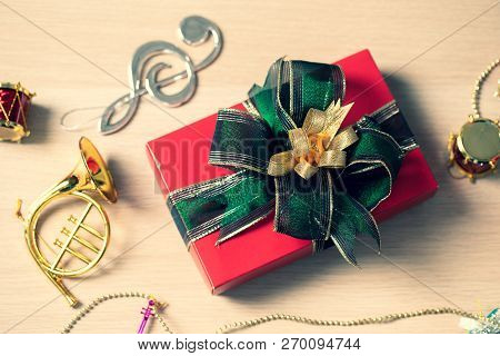 Close Up Of One Beautiful Red Gift Box Wrapped With Green Ribbon Set On Wood Board, Decorate With Ar