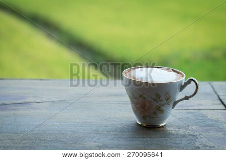 Coffee cup on blank wooden table selective focus with copy space.