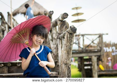 Little Asian Girl Smile And Hold Pink Umbrella Selective Focus With Copy Space.