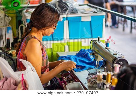 Bangkok, Thailand - November 2018: Woman Sewing On A Sewing Machine Running A Tailor Shop On A Stree